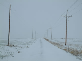 Snow covered road meets white sky horizon